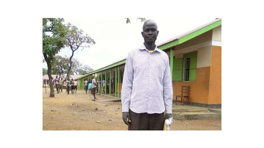 Akoy stands in a schoolyard. In the background you can see the school and some puple